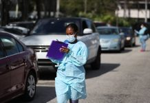 Health care staff from the FoundCare center wear protective gear as they help people who called to setup a drive through appointments to be tested for the coronavirus in the centers parking lot on March 16, 2020 in West Palm Beach, Florida. (Photo by Joe Raedle/Getty Images)