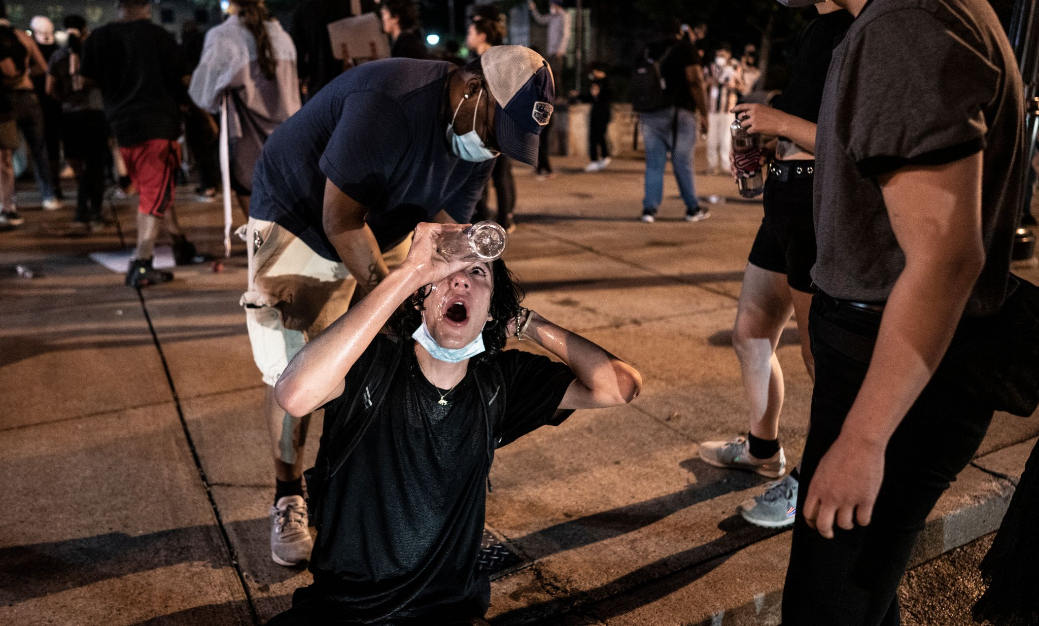 Nashville, Tenn., May 30 - A man rinses his eyes after tear gas was released by Metro Nashville Police.