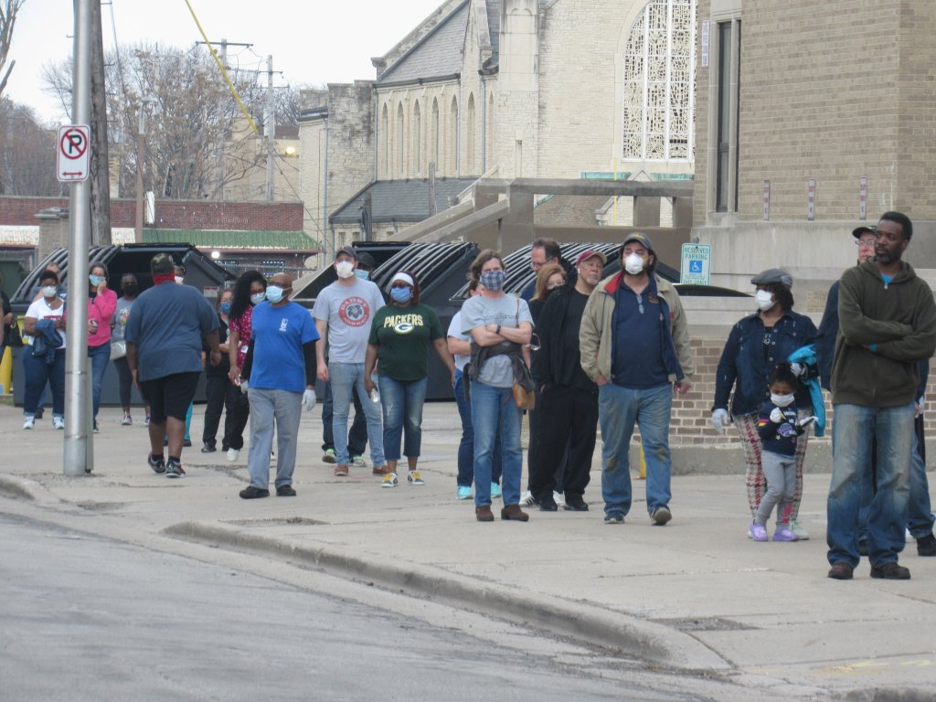 Voters wearing masks wait in line to vote in Milwaukee's April 7 primary. Only staff five polling sites out of 180 were staffed because of the coronavirus pandemic. (Photo by Isiah Holmes/ Wisconsin Examiner)