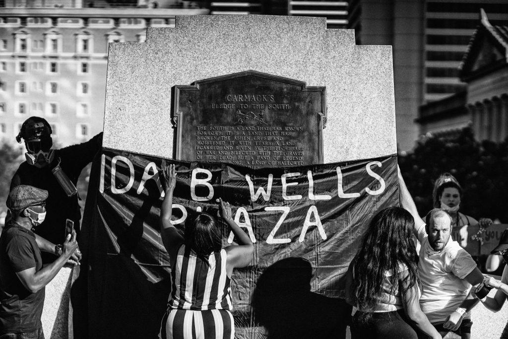 "Nashville, Tenn. - Hanging a banner on the former statue of Edward Carmack designating the space ""Ida B. Wells Plaza."" (Photo: Alex Kent)"