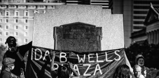 "Nashville, Tenn. - Hanging a banner on the former statue of Edward Carmack designating the space ""Ida B. Wells Plaza."" (Photo: Alex Kent)"