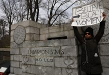 A woman stands beside the empty pedestal where a statue of J. Marion Sims, a surgeon celebrated by many as the father of modern gynecology, was taken down from its pedestal at Central Park and East 103rd Street on April 17, 2018 in New York City. A New York City panel decided to move the controversial statue after groups demanded its removal as many of Sims medical breakthroughs came from experimenting on black slaves without anesthesia. (Photo by Spencer Platt/Getty Images)