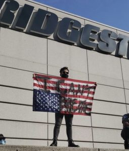 A protestor stands on a wall outside Bridgestone Arena in downtown Nashville. (Photo: Dulce Torres Guzman)