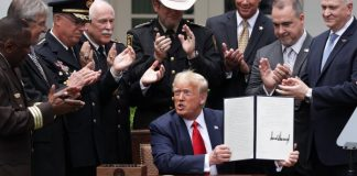 Donald Trump holding executive order and surrounded by law enforcement