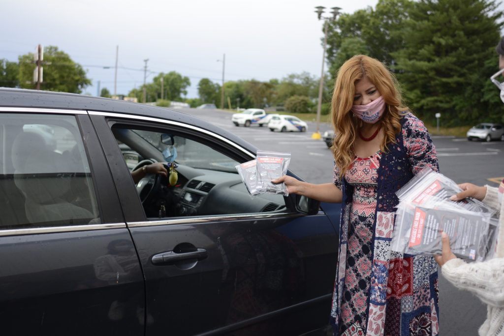Veronica Salcedo, a journalist with Nashville Noticias, distributes personal protective gear at a drive up event. (Photo: Dulce Torres Guzman/Tennessee Lookout)
