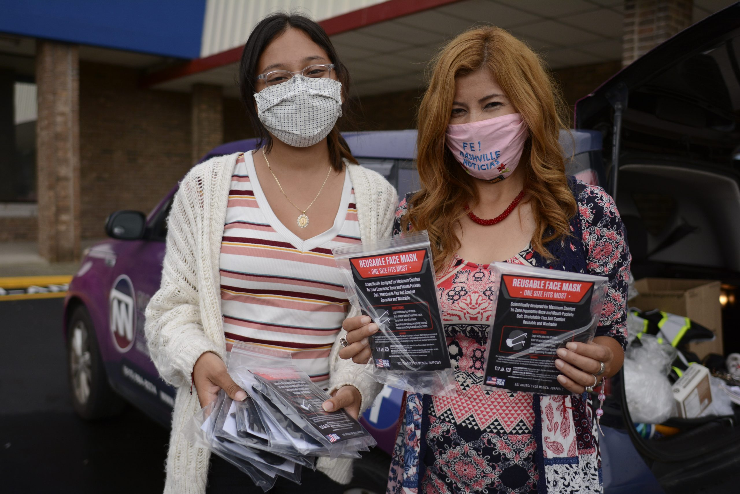 Veronica Salcedo, a journalist with Nashville Noticias, and a volunteer distribute personal protective gear at a drive through community event. (Photo: Dulce Torres Guzman/Tennessee Lookout)