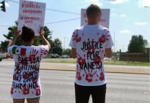 A couple holds signs for Vanessa Guillén across from the main entrance to Fort Campbell.(Photo: Celia Darrough)