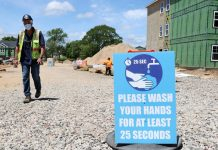 """A construction worker walks past a sign the reads """"Please wash your hands for at least 25 seconds"""" at a construction site. (Photo by Al Bello/Getty Images)"""
