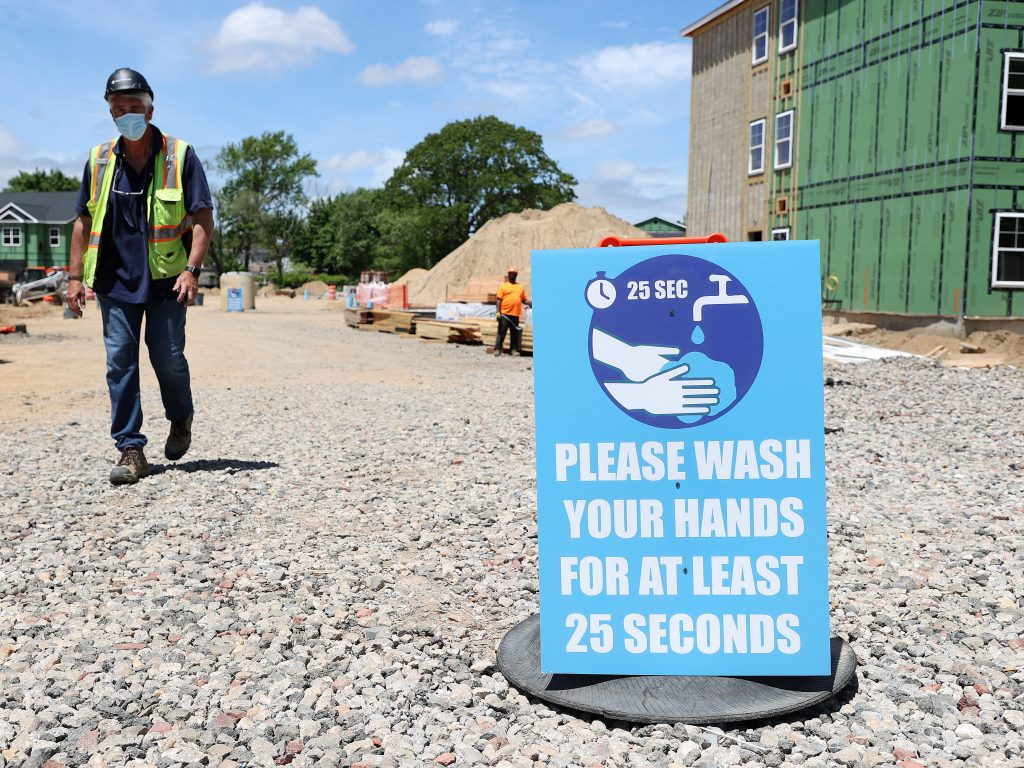 A construction worker walks past a sign the reads