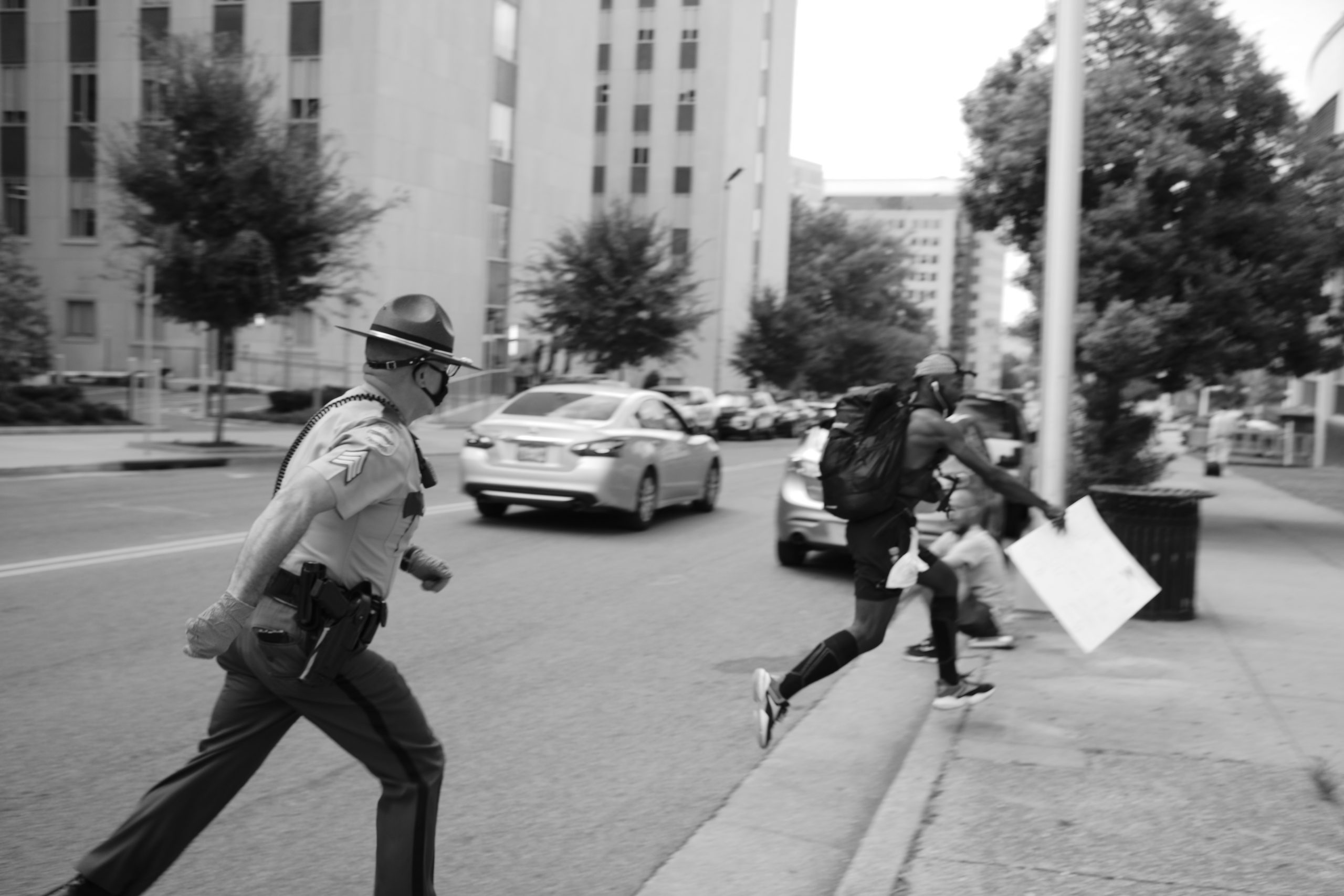 A Tennessee state trooper chases a protester holding a sign on 5th Avenue, N. in Nashville, across from the Cordell Hull Office Building. (Photo: Ray Di Pietro)