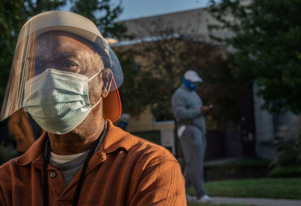 Early voter Marvin Williams took precautions by wearing a mask and a face shield while standing in line on the first day of early voting at the Howard Building in Nashville. Photo: John Partipilo)
