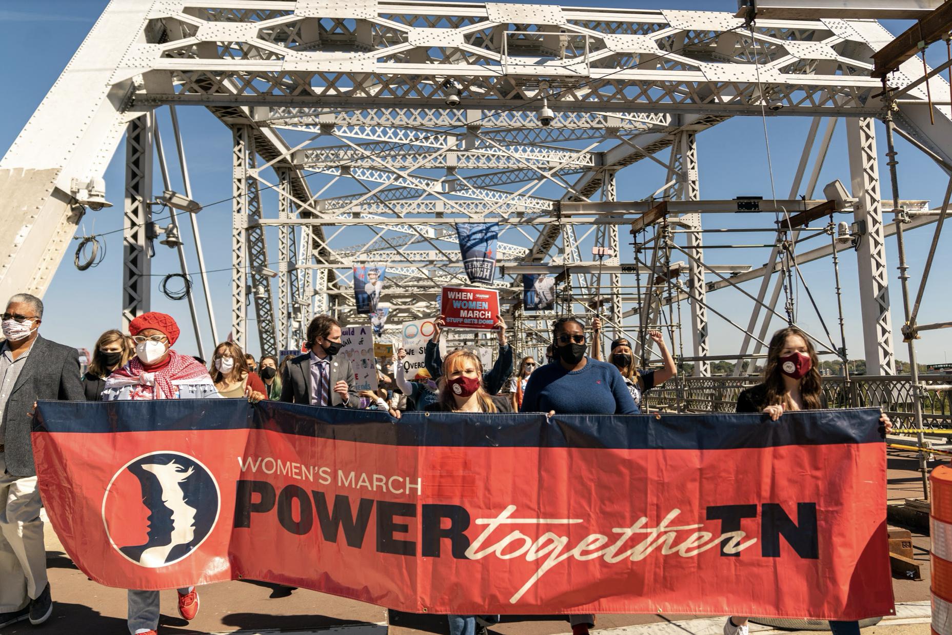 Nashville, Tenn., Oct. 17 - Leaders of the Power Together Women's March cross the John Seighenthaler Pedestrian Bridge. (Photo: Alex Kent)