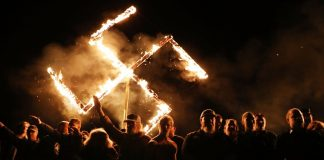 DRAKETOWN, GA - APRIL 21: Members of the National Socialist Movement, one of the largest neo-Nazi groups in the US, hold a swastika burning after a rally on April 21, 2018 in Draketown, Georgia. Community members had opposed the rally in Newnan and came out to embrace racial unity in the small Georgia town. Fearing a repeat of the violence that broke out after Charlottesville, hundreds of police officers were stationed in the town during the rally in an attempt to keep the anti racist protesters and neo-Nazi groups separated. (Photo by Spencer Platt/Getty Images)