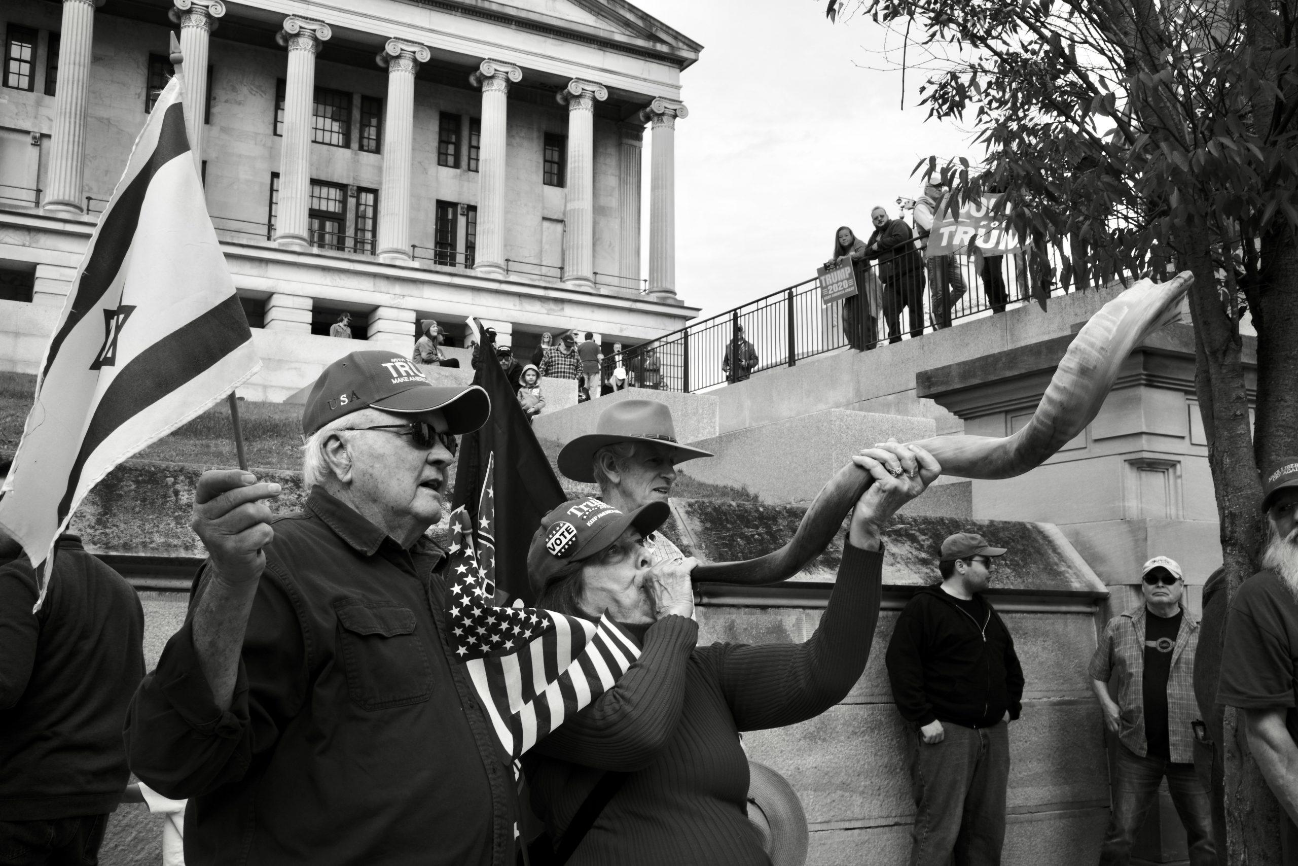A woman blows a vuvuzela at Saturday's protest. (Photo: Ray Di Pietro)
