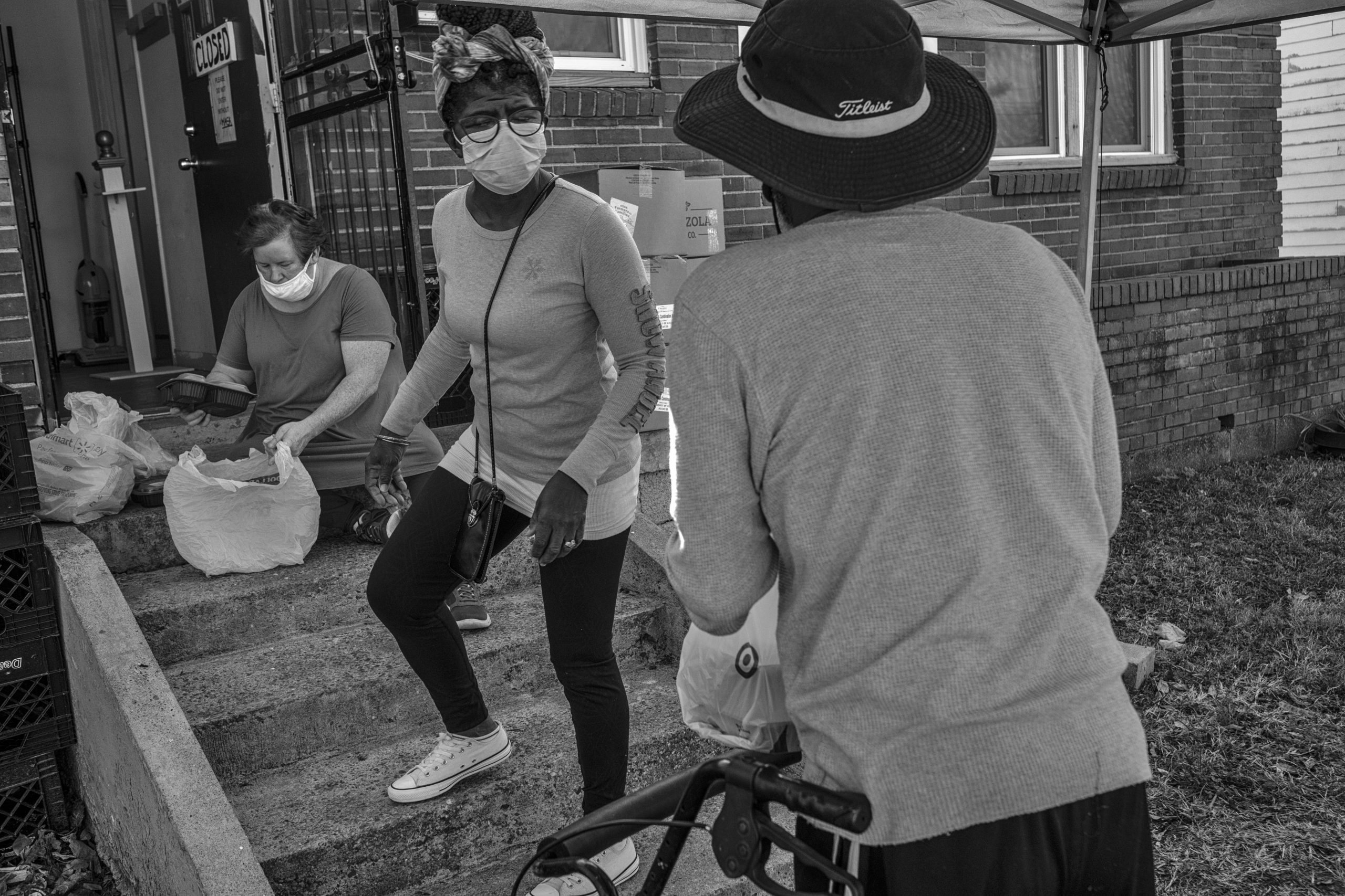 """Quanita Thomas, fondly known as """"Q"""" (center) hands out a food basket to Carlos Williams who lives in the North Nashville neighborhood. Thomas is also an associate pastor at the Historic First Community Church in North Nashville. (Photo by John Partipilo"""