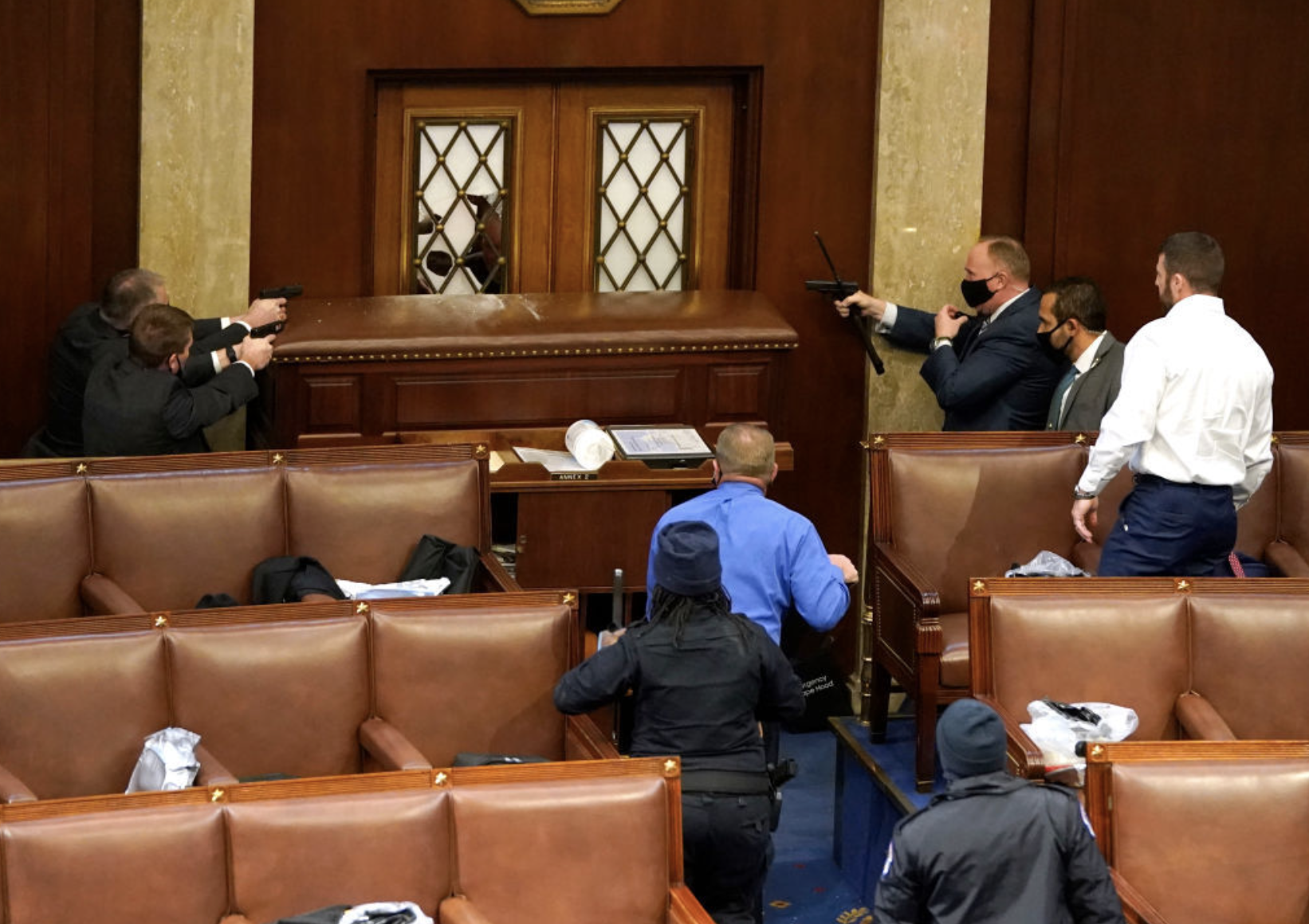 U.S. Capitol police officers point their guns at a door that was vandalized in the House Chamber during a joint session of Congress on January 06, 2021 in Washington, DC. (Photo by Drew Angerer/Getty Images)