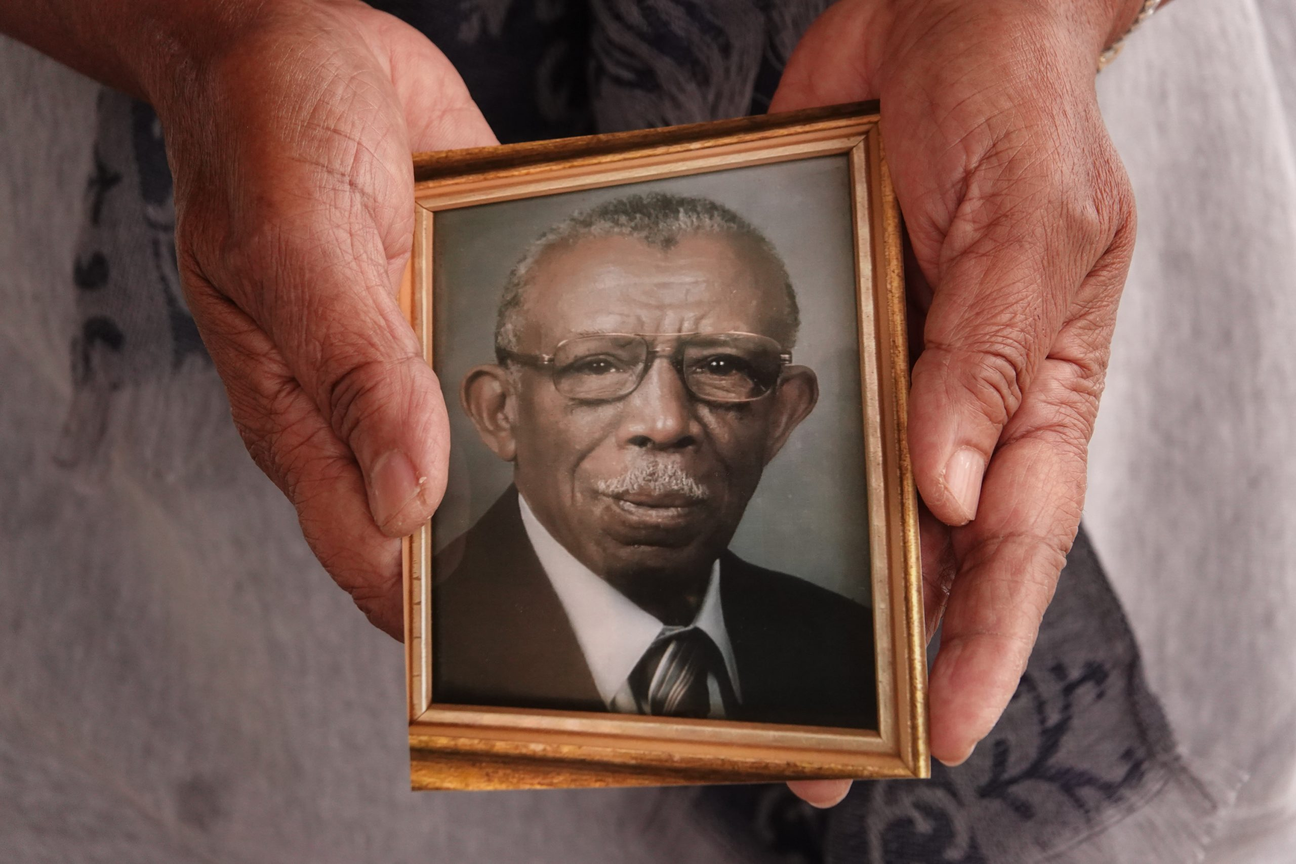 Joyce Christian of Somerville, Tennessee holds a photo of her father Freddie Lee Tyson. She is a retired nurse who wants to encourage people in the African American community to take the Covid-19 vaccine. Her father, was unknowingly a part of the Tuskegee syphilis study. What happened to her father, led to the establishment of biomedical ethics committees. These committees were established to set ethical criteria to ensure what happened to her fathers would not happen again. (Photo by © Karen Pulfer Focht)