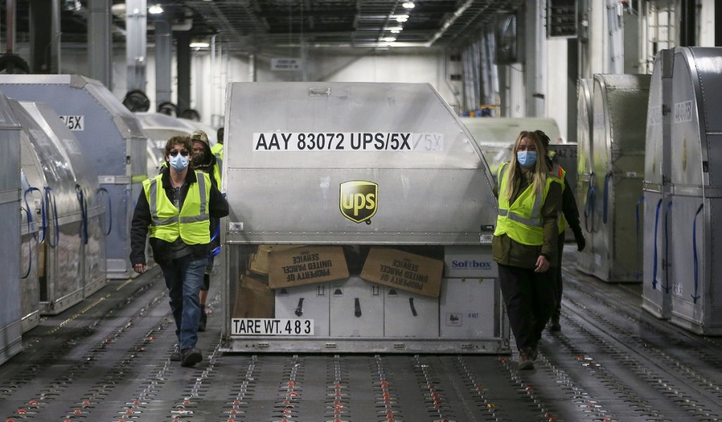 UPS employees move one of two shipping containers containing the first shipments of the Pfizer and BioNTech COVID-19 vaccine inside a sorting facility December 13, 2020 in Louisville, Kentucky. The flight originated in Lansing, Michigan. (Photo by Michael Clevenger - Pool/Getty Images)