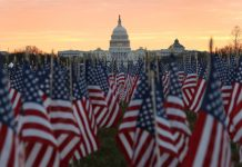 WASHINGTON, DC - JANUARY 18: The U.S Capitol Building is prepared for the inaugural ceremonies for President-elect Joe Biden as American flags are placed in the ground on the National Mall on January 18, 2021 in Washington, DC. The approximately 191,500 U.S. flags will cover part of the National Mall and will represent the American people who are unable to travel to Washington, DC for the inauguration. (Photo by Joe Raedle/Getty Images)