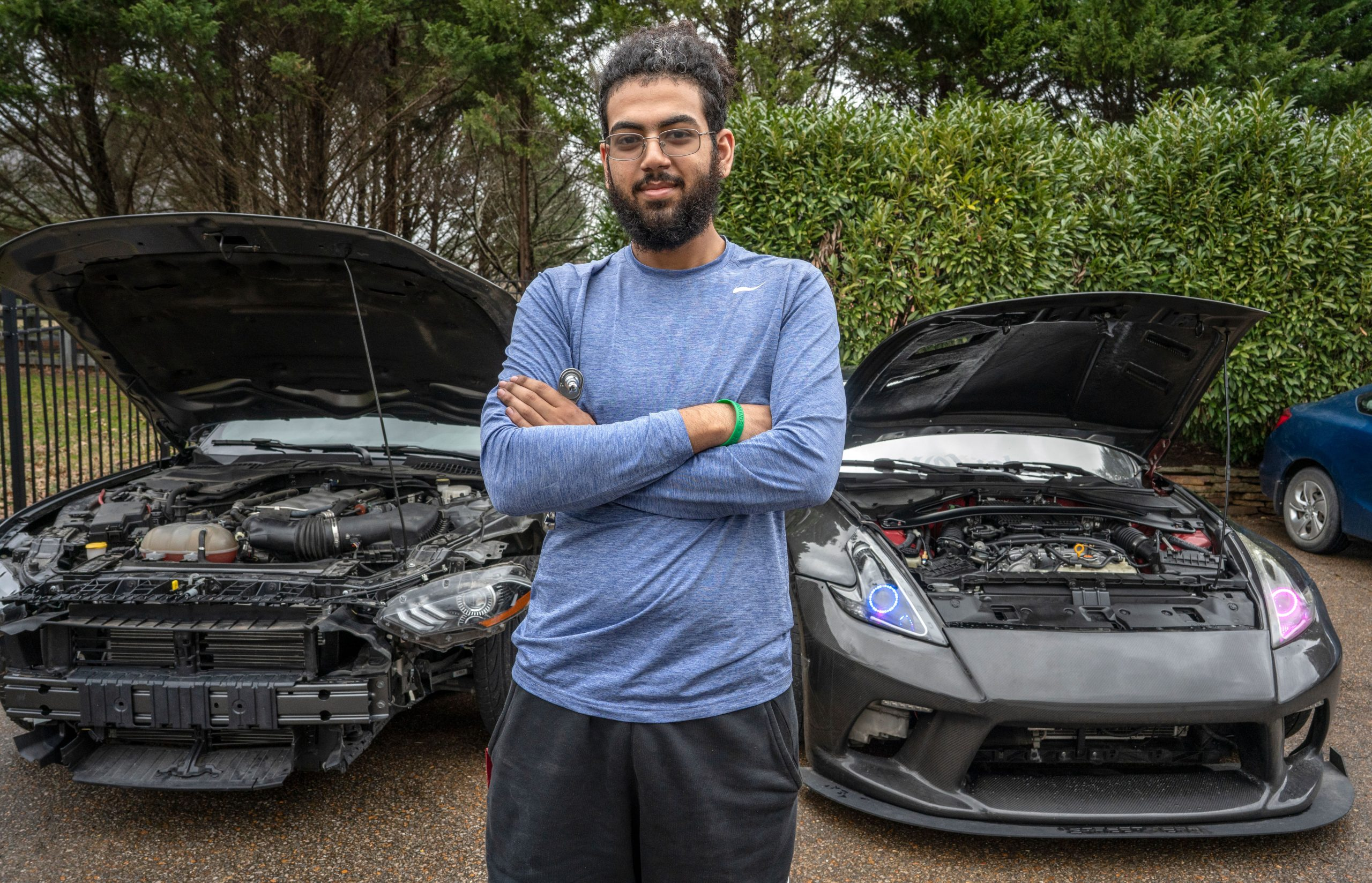 Jacob Yousief stands in front of two of his cars. Yousief learned how to repair cars himself to save money. (Photo: John Partipilo)