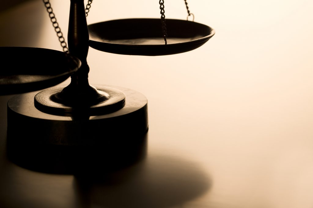 Scales of justice with back-light on wood table.