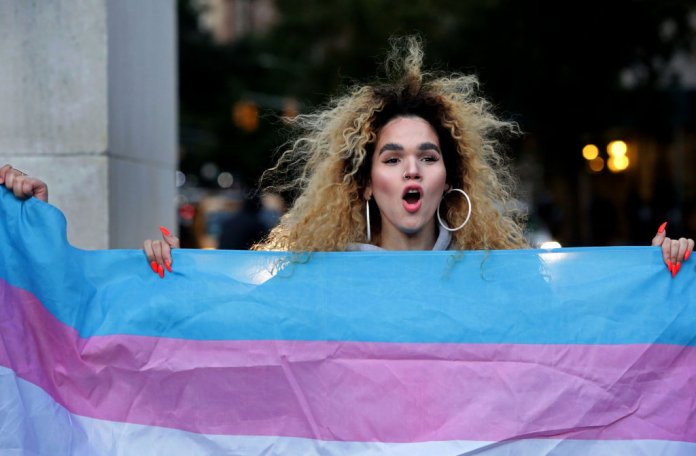A transgender woman hold a transgender pride flag at a rally for LGBTQ rights in New York. (Photo by Yana Paskova/Getty Images.)