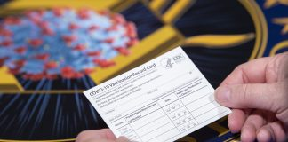 A Department of Health and Human Services employee holds a COVID-19 vaccine record card Nov. 13, 2020, in Washington D.C. The cards will be sent out as part of vaccination kits from Operation Warp Speed, which is an effort by several U.S. government components and public partnerships to facilitate the development, manufacturing and distribution of COVID-19 vaccines, therapeutics and diagnostics. (DoD photo by EJ Hersom)