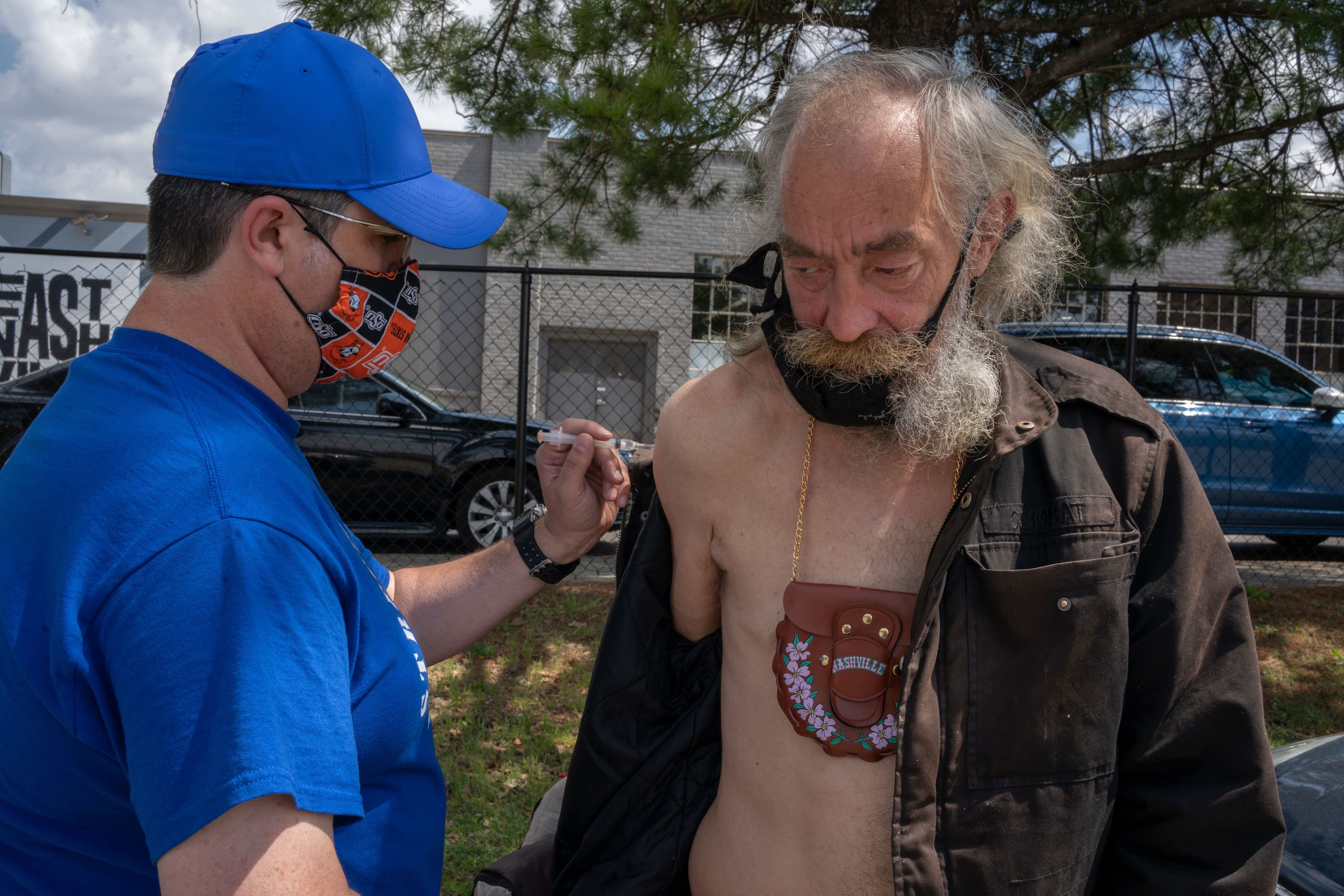 Homeless man Steve Nelson get his Johnson and Johnson vaccine from RN Jeremy McCraw of Neighborhood Health in the parking lot of Holy name Church. (Photo: John Partipilo)