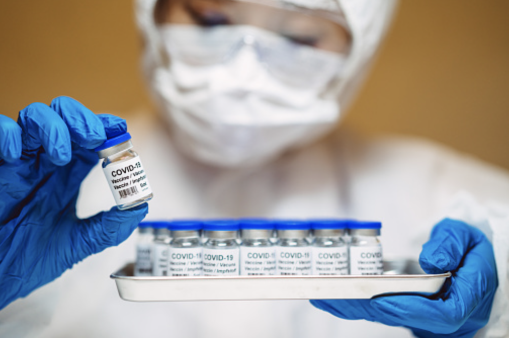 Healthcare professional in protective gloves and workwear holding and organizing a tray of COVID-19 vaccine vials. The professional is carrying out research on COVID-19 vaccine in laboratory. (Getty Images)