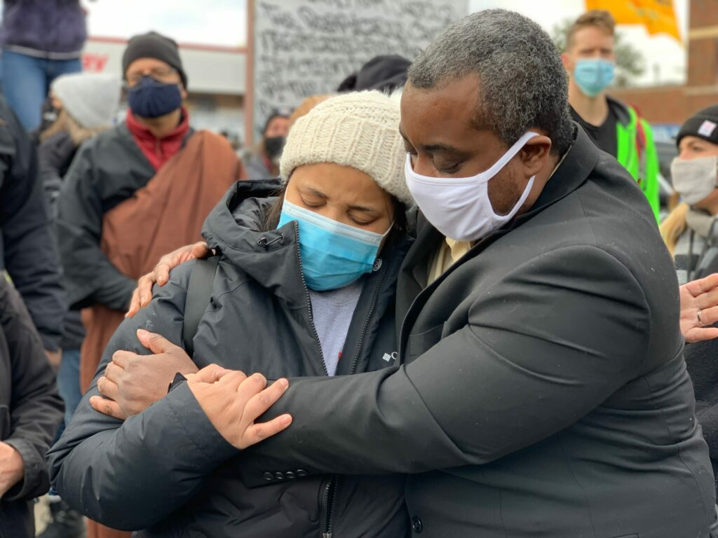 Rev. Lawrence Richardson of the Linden Hills United Church of Christ (right), offers comfort to Rev. Jia Starr Brown of First Covenant Church (left) at George Floyd Square. Photo by Ricardo Lopez/Minnesota Reformer.