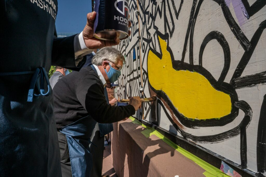 Nashville Mayor John Cooper paints part of a mural on a damaged Second Avenue building. (Photo: John Partipilo)