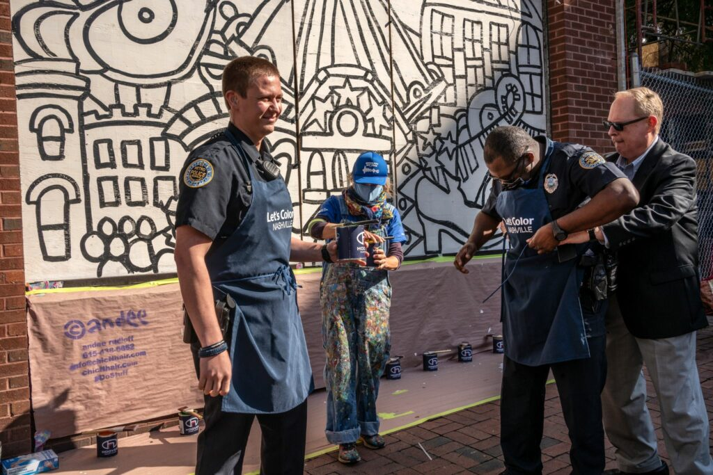 Metro Nashville Police Public Affairs Manager Don Aaron, right, helps an officer cover his uniform with an apron before painting. (Photo: John Partipilo)