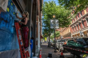 Dressing up damaged buildings on Second Avenue with paint. (Photo: John Partipilo)