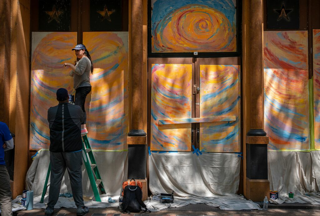A volunteer paints a boarded up window on Nashville's Second Avenue. Many buildings on the street were heavily damaged by a Christmas Day suicide bomb. (Photo: John Partipilo)