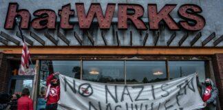 "Protestors hold a banner saying, ""No Nazis in Nashville"" outside hatWRKS in Nashville during a Saturday protest. (Photo: John Partipilo)"