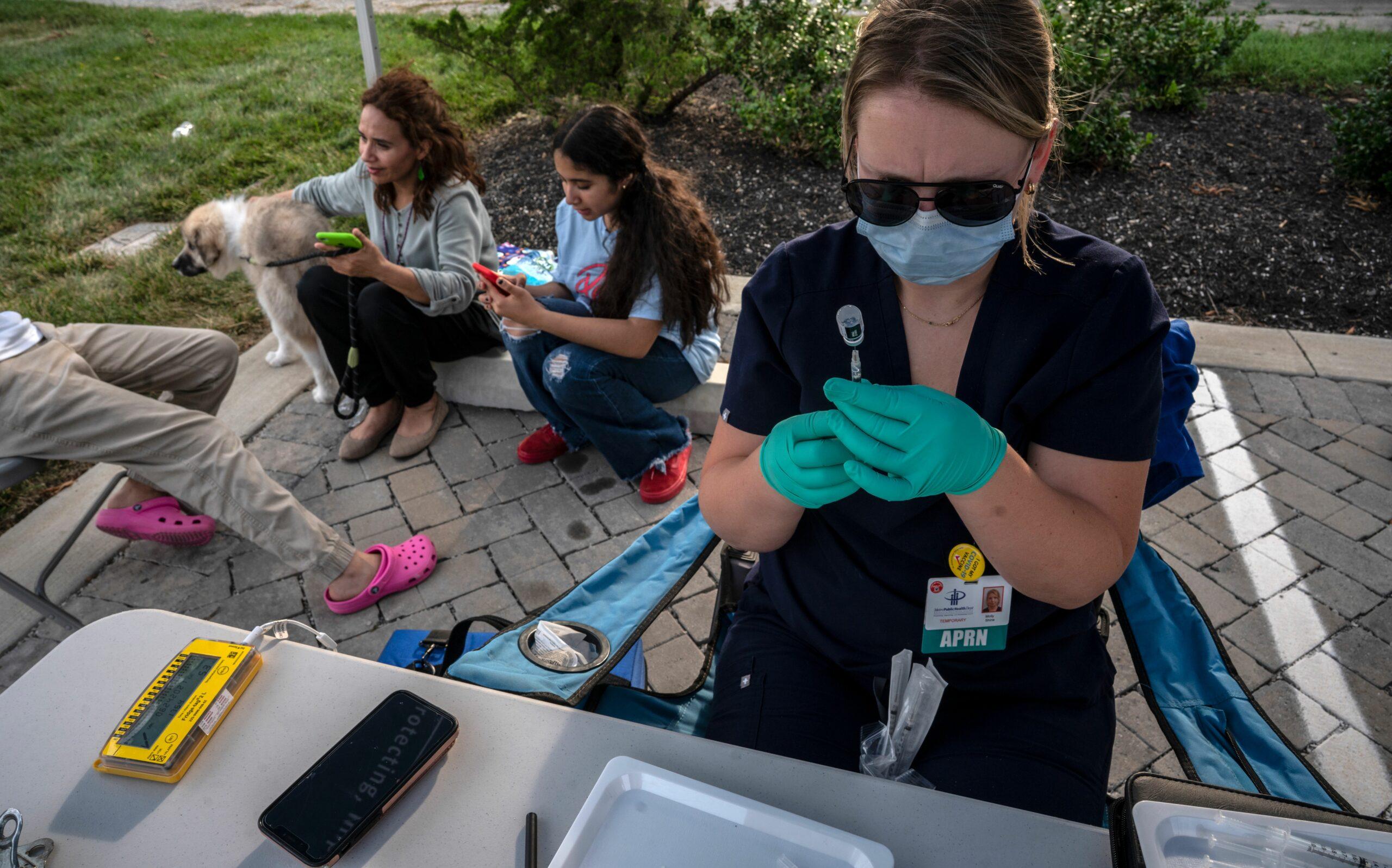 Metro Public Healthy Molly Shine preps a vaccine while sister Maya and Sara Gana wait at a recent Nashville mobile vaccine clinic. (Photo: John Partipilo)