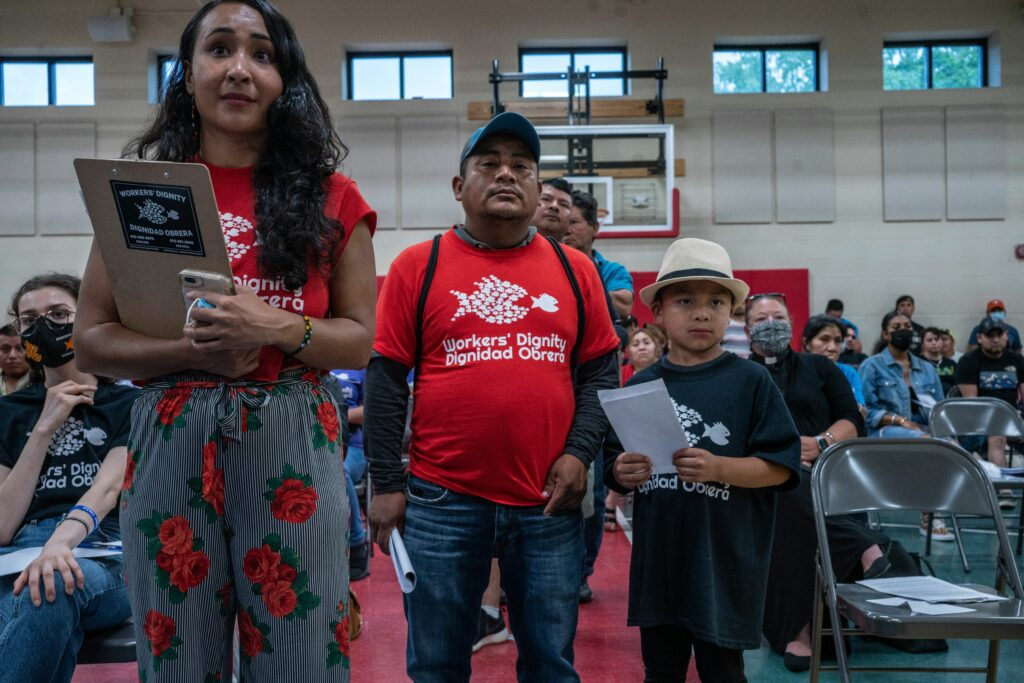 From left, Cecilia Prado with Workers Dignity waits with Mosaic apartment tenant Nicolas Alvarado and son Nery, 7, who wait to speak to management about eviction threats. (Photo: John Partipilo)