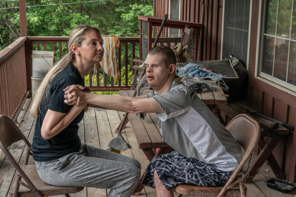 Drama Bryant, 38, with her brother Jay, 32, on the front porch of their family's home in Greene County. She is his primary caretaker. (Photo: John Partipilo