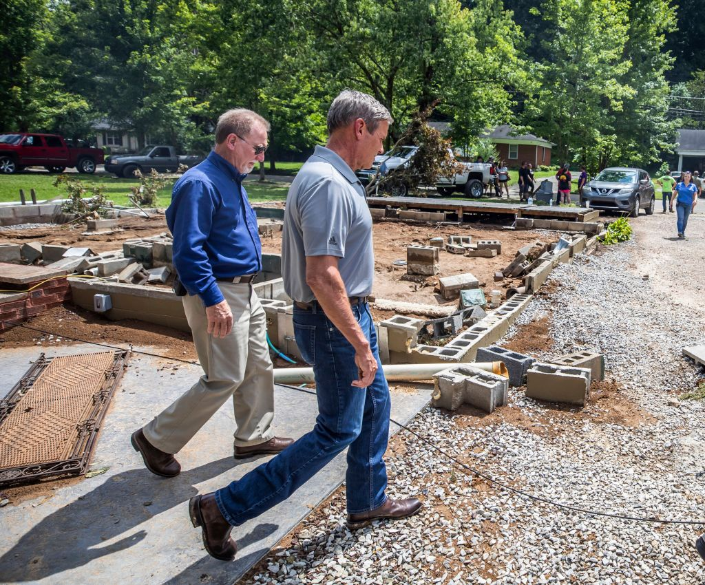 WAVERLY, TENNESSEE - AUGUST 22: Tennessee Gov. Bill Lee (R) walks past a home swept off its foundation in catastrophic floods August 22, 2021 in Waverly, Tennessee. At least 22 people were killed and 50 others remained missing today after flash floods swept through middle Tennessee, according to officials. (Photo by Alan Poizner-Pool/Getty Images)
