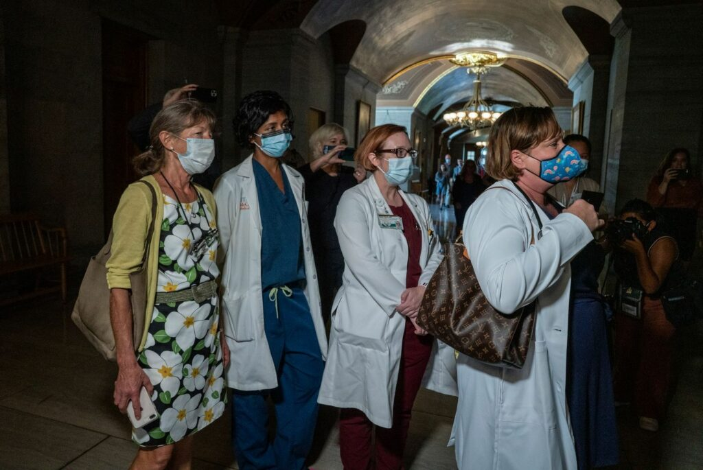 A group of doctors representing St. Jude's Children's Research Hospital attempt to get Gov. Bill Lee's attention after his Thursday press conference. (Photo:John Partipilo)