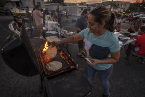 Woman cooks tortillas at a charity event.