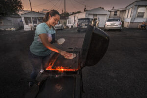 Woman heats tortillas on a grill.