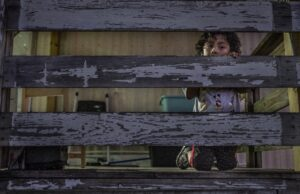 A child peeks through the weathered porch of his mobile home.