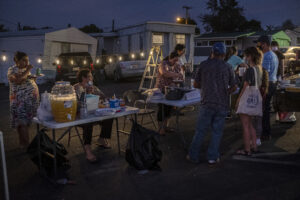 People crowd around mobile home tenants serving food.